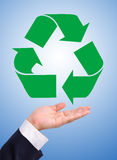 Recycling on a hand. Recycling symbol on a business man's hand over blue background Royalty Free Stock Photos