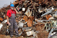 Recycling industry, heap of old metal and worker Stock Photo