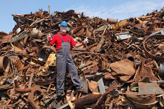 Recycling industry, worker gesture at heap of old metal Royalty Free Stock Image