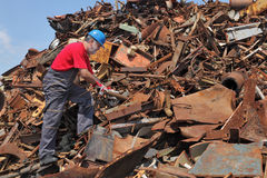 Recycling industry, worker at heap of old metal. Worker inspecting heap of scrap metal ready for recycling Stock Photo