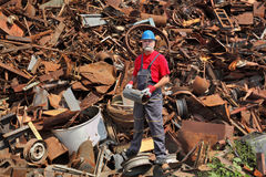 Recycling industry, worker stand at heap of old metal Stock Photo