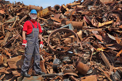 Recycling industry, worker standing at heap of old metal Stock Photo