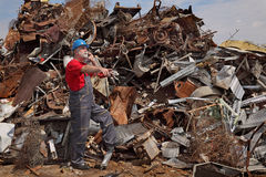 Recycling industry, worker using phone at heap of old metal Stock Photos