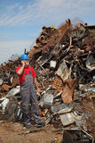 Recycling industry, worker using phone and heap of old metal Royalty Free Stock Image