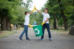 Group of kids volunteer help garbage collection charity environment, selective soft focus. Team work. Recycling a plastic bottle. Recycle a plastic bottle in a Royalty Free Stock Photos