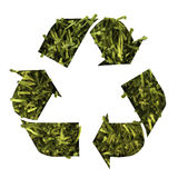 Recycling Polyester. Recycling icon in front of a polyester carpet, wich looks like grass Royalty Free Stock Photography