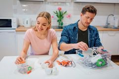 Recycling, reuse, energy. Young couple sorting batteries, other electronic waste into containers with recycling symbol. Recycling, reuse, energy. Young couple royalty free stock photos
