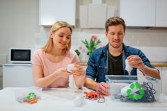 Recycling, reuse, energy. Young family sorting light bulbs, batteries, other electronic waste into containers with. Green recycling symbol while sitting at royalty free stock photography