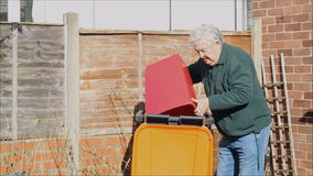 Recycling rubbish in a a trash can or rubbish bin. Recycling rubbish in a trash can or rubbish bin. Senior man emptying rubbish into a wheelie bin stock video footage