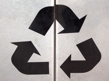 Recycling sign. Black recycling sign on silver background Royalty Free Stock Images