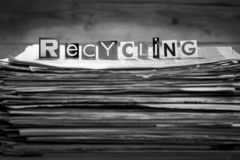 Recycling sign on a pile of old newspapers. royalty free stock photography