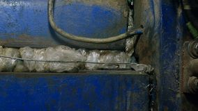 Old and dirty press machine presses household waste or trash. Recycling sorting facility and processes, plant for sorting garbage, dirty job stock video footage