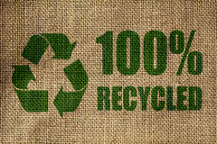 Recycling symbol. And one hundred per cent recycled sign on the side of a hessian bag in green Royalty Free Stock Image