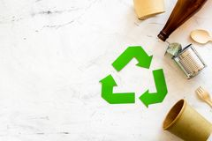 Recycling symbol and different garbage on marble background top view copyspace. Ecology concept. Recycling symbol and different garbage. Paper cup, spoon, fork stock photos