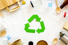 Recycling symbol and different garbage on marble background top view. Ecology concept. Recycling symbol and different garbage. Paper bag, cup, spoon, fork royalty free stock photo