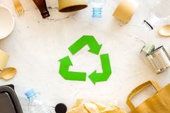 Recycling symbol and different garbage on marble background top view. Ecology concept. Recycling symbol and different garbage. Paper bag, cup, spoon, fork stock image
