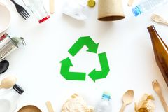 Recycling symbol and different garbage on white background top view. Ecology concept. Recycling symbol and different garbage. Paper cup, spoon, fork, plastic royalty free stock photos
