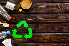 Recycling symbol and different garbage on wooden background top view copyspace. Ecology concept. Recycling symbol and different garbage. Plastic cup, spoon stock photos