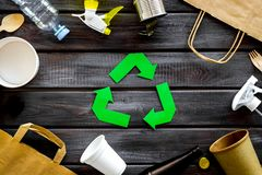 Recycling symbol and different garbage on wooden background top view. Ecology concept. Recycling symbol and different garbage. Paper bag, cup, spoon, fork stock photo