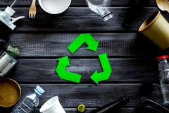 Recycling symbol and different garbage on wooden background top view. Ecology concept. Recycling symbol and different garbage. Paper cup, spoon, fork, plastic stock photos