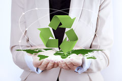 Recycling Symbol over earth map in woman hands Royalty Free Stock Photos