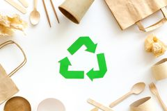 Recycling symbol and paper garbage on white background top view. Ecology concept. Recycling symbol and paper garbage. Bag, cup, flatware on white background top royalty free stock photo
