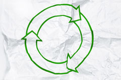 Recycling symbol on white crumpled paper. Green recycling symbol on white crumpled paper Stock Photos