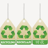 Recycling tags. Signs. English, Spanish, Chinese inscribed Royalty Free Stock Photos