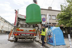 Recycling truck picking up trash bins. Sofia, Bulgaria - May 26, 2016: A sanitary worker is picking up trash bins with his recycling truck. Bins for separately royalty free stock photos