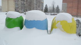 Recycling waste containers bin winter snowstorm snow fall. Colorful recycle waste containers bins near flat houses and winter blizzard snowstorm snow fall stock video