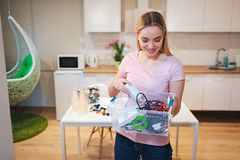 Recycling. Young smiling woman holding electronic waste in the container with green recycle icon on kitchen background. Recycling. Young smiling woman holding royalty free stock photo