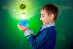Recyclingsconcept, weinig jongen die een lichte bal in hand houden Stock Foto's