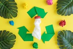 Recyclingsteken met plastic fles en tropische palmbladen met verfrommeld document op geel stock afbeeldingen