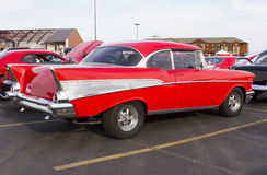 Red 1957 Chevy Rear & Side View. A vintage red 1957 Chevy shown from the side.  Showcasing the famous rear tail fins.  Classic Crager steel wheels, dual exhaust Stock Photography
