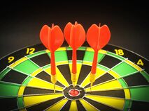 Red 3 Dart Pin on Black Green and Yellow Dartboard Royalty Free Stock Photography