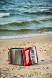 A red accordion on a beach. In Summer Royalty Free Stock Photos