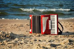 A red accordion on a beach. In Summer Royalty Free Stock Photography