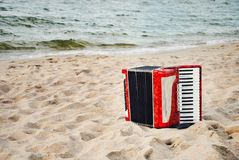 A red accordion on a beach. In Summer royalty free stock photo