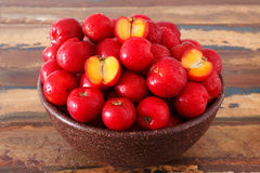 Red acerola - malpighia glabra, tropical fruit  in bowl on table. Selective focus Stock Photo