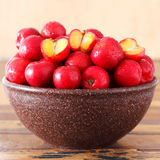 Red acerola (malpighia glabra), tropical fruit in brown bowl. Selective focus. Square shape Royalty Free Stock Photography