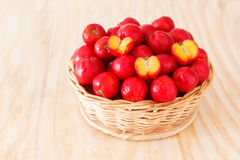 Red acerola - malpighia glabra, tropical fruit in wicker busket. With copy space. Selective focus Stock Photo