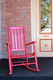 Red adirondack chair on front porch. Red painted Adirondack chair on front porch of home, inviting visitors to sit and relax for a minute Royalty Free Stock Photos
