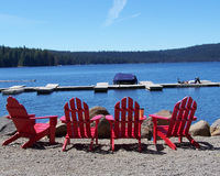 Red Adirondack Chairs- Four by the Lake Stock Image