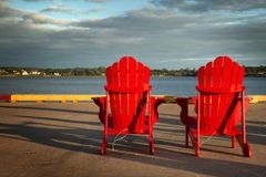 Red adirondack chairs in front of water Royalty Free Stock Photos