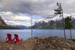 Red Adirondack Chairs at Lake Minnewanka in Banff National Park. Red Adirondack Chairs and Dramatic Stormy Sky Landscape at Lake Minnewanka on Windy Autumn Day Stock Photos