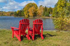 Red Adirondack Chairs on a Lake Shore. Two red Adirondack Chairs on a lake shore on a sunny autumn day Stock Image