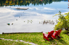 Red Adirondack Chairs on the Shore of a Lake Stock Image