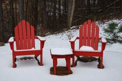 Red Adirondack chairs in the snow Stock Photography