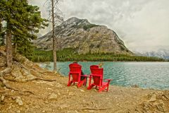 Red Adirondack chairs. Two red Adirondack chairs one man sit in front of Lake  mountains fog in Banff Royalty Free Stock Photos