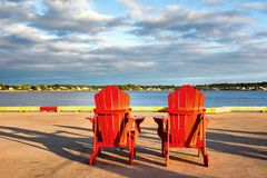 Red adirondack chairs. Two red adirondack chairs on the quayside at Charlottetown, Prince Edwad Island, Canada Stock Photo